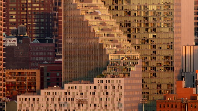 A grouping of architectural buildings on the West Side of Manhattan during dusk.