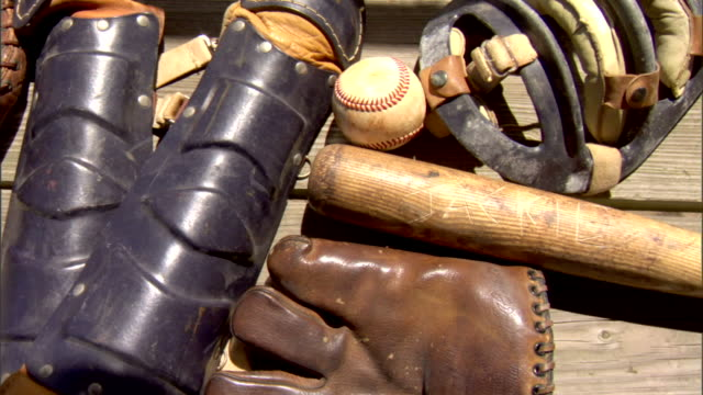 MS Grouping of vintage glove bat baseball catcher's face mask shin guard on bench