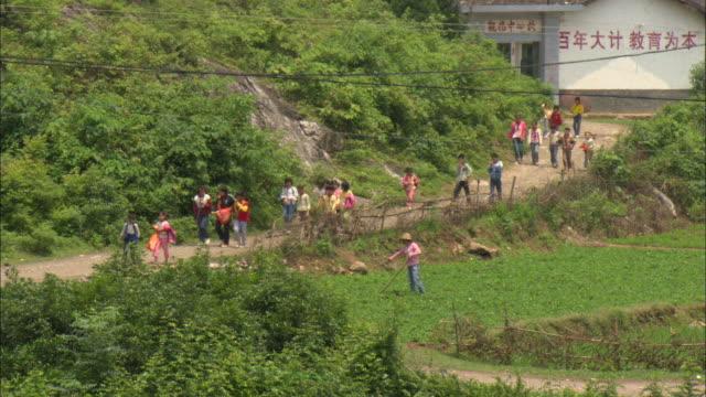 WS HA Groups of children leaving school and walking down path in village, Guilin, Guangxi Zhuang Autonomous Region, China
