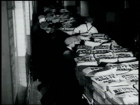 vidéos et rushes de groups of men pushing flat carts filled w/ folded newspapers lining carts up w/ backs of waiting trucks pushing newspapers into trucks trucks on road... - donner
