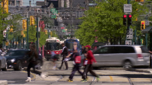 vídeos de stock, filmes e b-roll de groups of people cross a busy intersection in toronto canada in front a busy intersection with streetcars on spadina ave in downtown toronto. - canadá