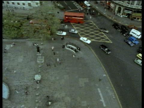 Groups of people pigeons and traffic rush around Trafalgar Square
