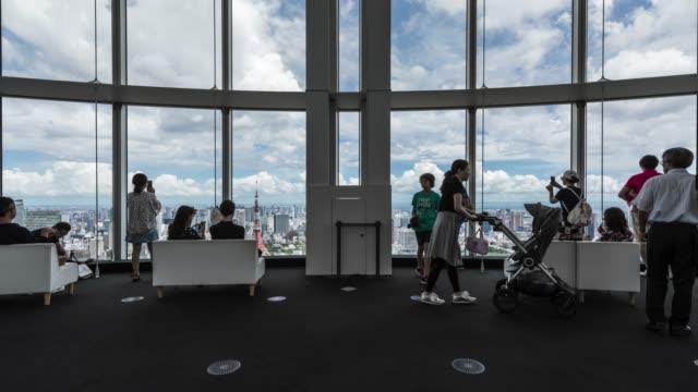 t/l ws el tu groups of people sightseeing tokyo skyline over large window in roppongi observatory deck - 自画像点の映像素材/bロール