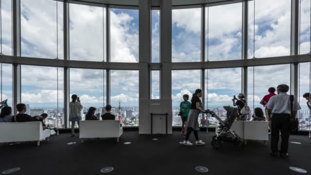 vídeos de stock, filmes e b-roll de t/l ws el zi groups of people sightseeing tokyo skyline over large window in roppongi observatory deck - ponto de observação