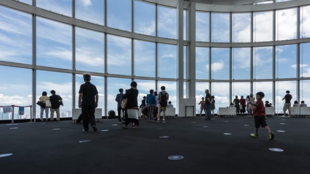 t/l ws el pan groups of people sightseeing tokyo skyline over large window in roppongi observatory deck - 自画像点の映像素材/bロール