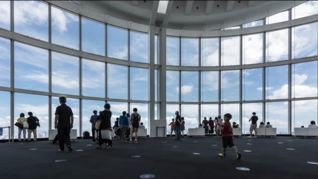 vídeos de stock, filmes e b-roll de t/l ws el zo groups of people sightseeing tokyo skyline over large window in roppongi observatory deck - ponto de observação