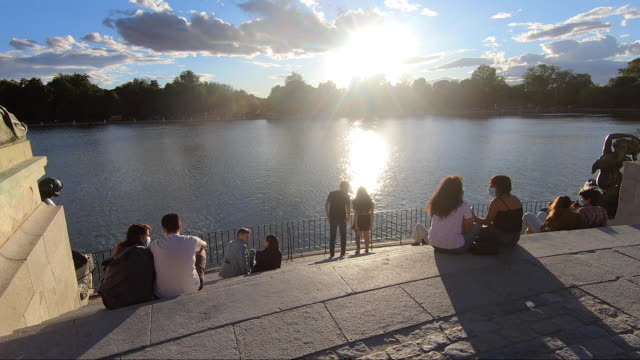 groups of people wearing face masks hang out at sunset at retiro park, one of the city's most iconic landmarks, in madrid, spain on august 29, 2020. - leisure activity stock videos & royalty-free footage