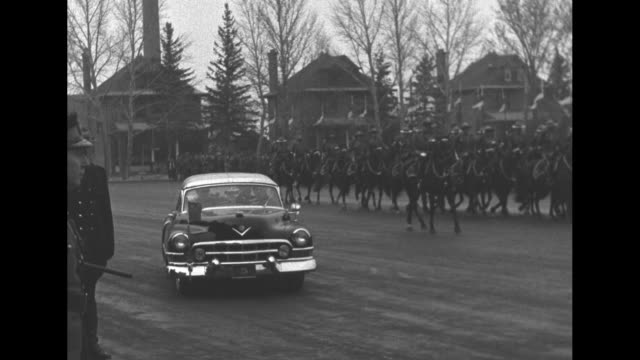 groups of royal canadian mounted police trot on wet street / cadillac sedan comes to stop with mounties trotting behind / line of mounties facing... - cadillac stock videos & royalty-free footage
