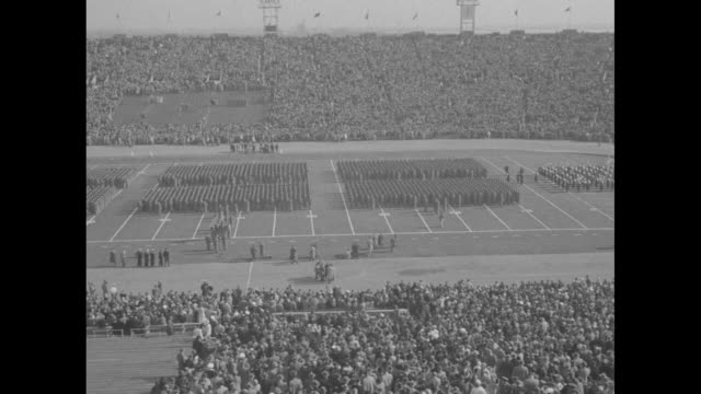 groups of us military academy cadets lined up on field of filled municipal stadium / qs us naval academy midshipmen march on field / view of... - チーム写真点の映像素材/bロール