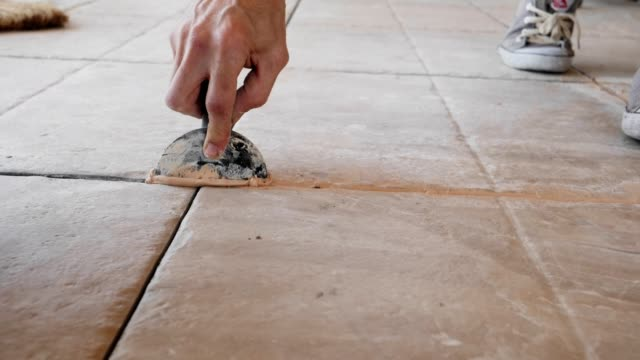 grouting, jointing of floor tiles, slow motion - installing stock videos & royalty-free footage