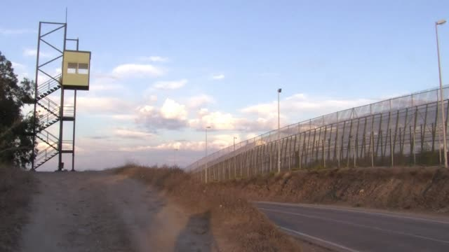 growing numbers of africans desperate to reach europe are trying to leap across a triple layer fence along the border of melilla a spanish city... - fence stock videos & royalty-free footage