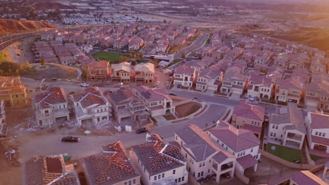 growing suburban housing development at sunset - aerial view - tract housing stock videos & royalty-free footage