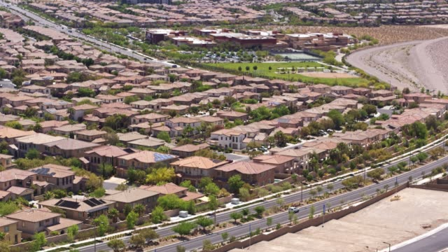 vídeos de stock e filmes b-roll de growing suburbs on the edge of las vegas - drone shot - expansão urbana