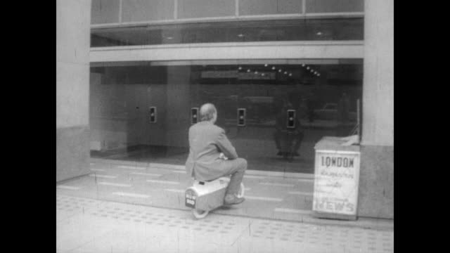 grown man in business suit riding along the street on a miniature motorbike in london / rides bike straight into a building lobby / goes onto... - 1967 stock videos & royalty-free footage