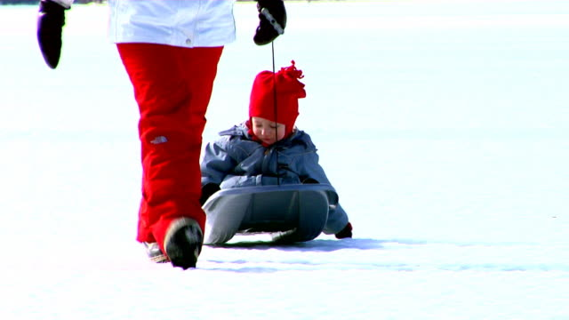 Grown-up pulling a little sledge with a child in Sweden.