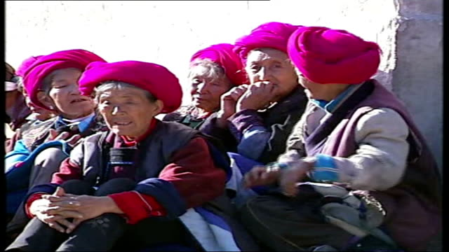 growth of christianity; cigu: small catholic church in mountain village elederly female villagers seated outside church man along smoking pipe local... - missionary stock videos & royalty-free footage