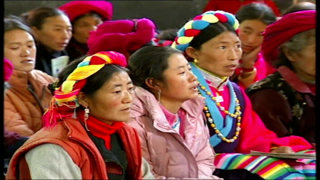 growth of christianity int father tao zhubin speaking to congregation local ethnic tibetan people seated listening to service cross painted on... - communist party stock videos and b-roll footage