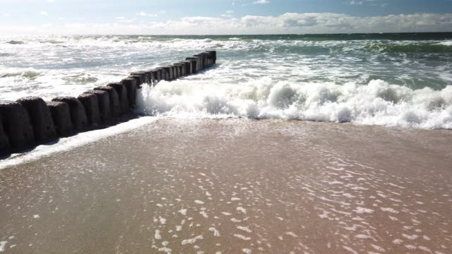 groynes and waves on the beach of sylt. blue sky. - tina terras michael walter stock-videos und b-roll-filmmaterial