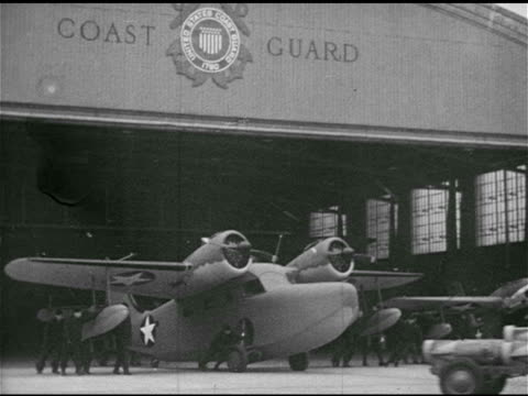 vídeos de stock, filmes e b-roll de grumman goose amphibious aircraft being pushed out of hangar two grumman j4f1 - 1943