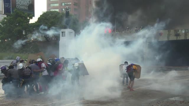 vídeos de stock e filmes b-roll de grupos de jovenes encapuchados cortaron la principal autopista de caracas para exigir elecciones generales en venezuela tras casi dos meses de... - exigir