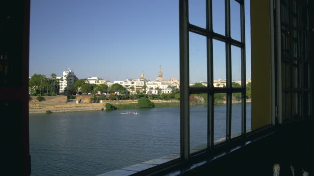 ws guadalquivir river and giralda through window of bar on triana side of puente isabel ii / seville, andalusia, spain - puente video stock e b–roll