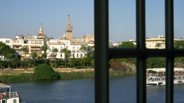 ms guadalquivir river and giralda through window of bar on triana side of puente isabel ii / seville, andalusia, spain - puente video stock e b–roll