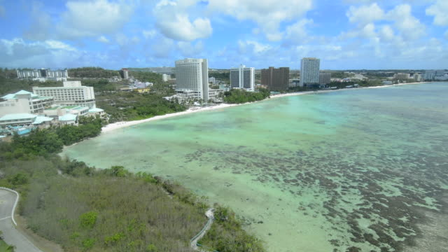 guam usa territory tumon bay hotels and beach from above with ocean beach and clouds - mariana islands stock videos and b-roll footage