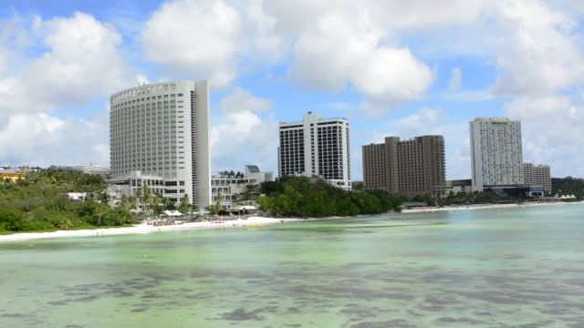 guam usa territory tumon bay hotels and beach from above with ocean beach and clouds - guam stock videos and b-roll footage