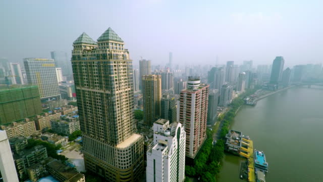 guangzhou skyline - drone flight passing skyscraper at daytime - spoonfilm stock-videos und b-roll-filmmaterial