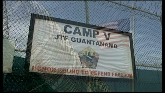 camp delta: ext barbed wire fence surrounding camp delta - us flag flying alongside 'camp v - jtf guantanamo' sign int us soldiers - guards - on... - guantanamo bay stock videos & royalty-free footage