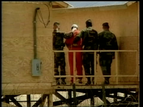 guantanamo bay camp xray captive wearing orange overall led along by us troops - camp x ray stock videos & royalty-free footage