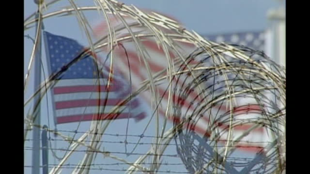 guantanamo bay detainee first to be convicted of terrorist offence; tx 12.9.2006 cuba: guantanamo bay: naval base: camp delta: ext american flag... - detainee stock videos & royalty-free footage