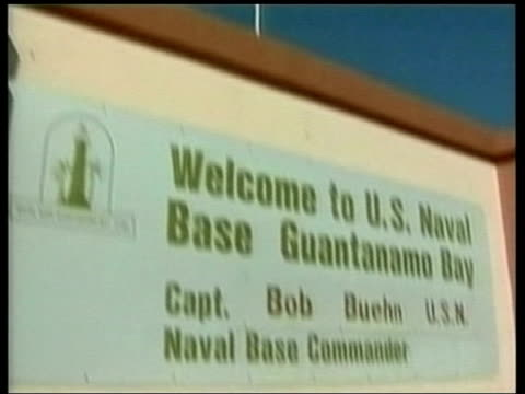 guantanamo bay - detainee treatment; itn cuba: guantanamo bay: ext lms us flag flying over entrance to guantanamo bay us naval base tilt down welcome... - guantanamo bay stock videos & royalty-free footage