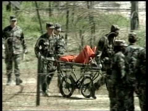 guantanamo bay: ext prisoner wheeled along at camp delta - gefangener stock-videos und b-roll-filmmaterial