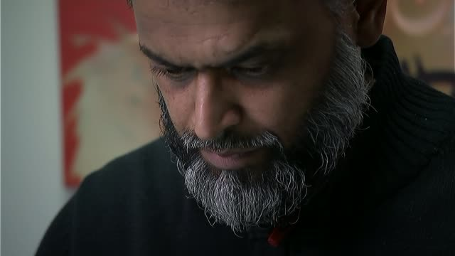 guantanamo detainee shaker aamer returns to uk; england: int moazzam begg set up looking at computer and interview sot - moazzam begg stock videos & royalty-free footage