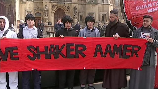 guantanamo detainee shaker aamer returns to uk; t17031502 / tx 17.3.2015 london: ext various shots of sons of shaker aamer and others holding banner... - detainee stock videos & royalty-free footage