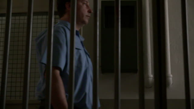 guard and interrogator walk in front of prison cell - interrogation stock videos and b-roll footage