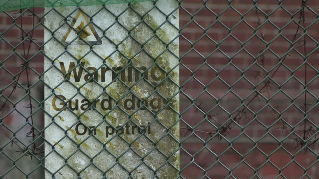 guard dog warning sign attached to napier barracks fencing on february 01, 2021 in folkestone, england. napier barracks, part of the disused somerset... - fence stock videos & royalty-free footage