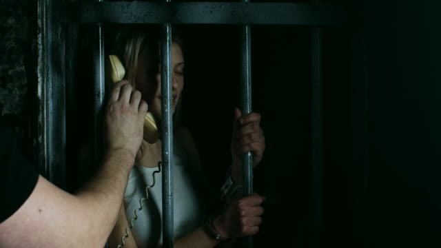 guard holding phone to prisoner in prison cell that she can talk - women prison stock videos & royalty-free footage