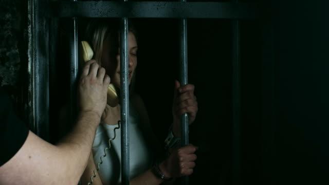 Wache halten Telefon Gefangenen im Gefängniszelle, die sie sprechen können