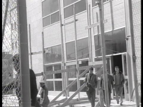 guard opens a gate for officials leaving the tel aviv court house where former gestapo official adolf eichmann awaits sentencing. - ゲシュタポ点の映像素材/bロール