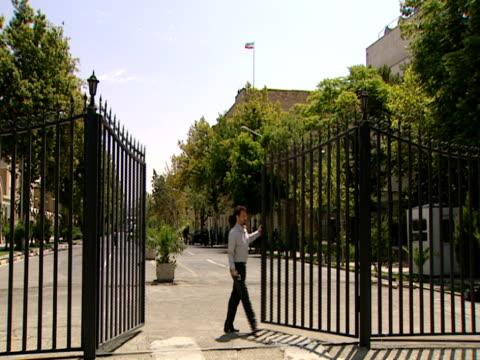 vidéos et rushes de guard opens a wrought iron gate / tehran, iran - format vignette
