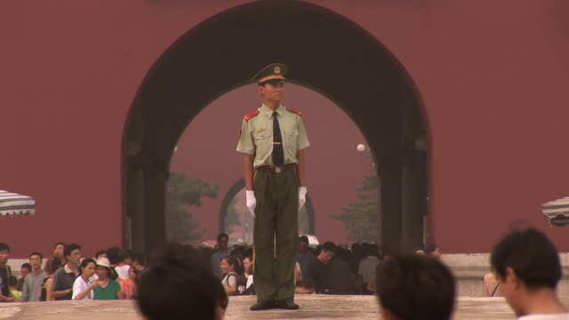 ws zo guard standing under portrait of chairman mao while tourists walk around at tiananmen square/ beijing, china - chinese language stock videos & royalty-free footage