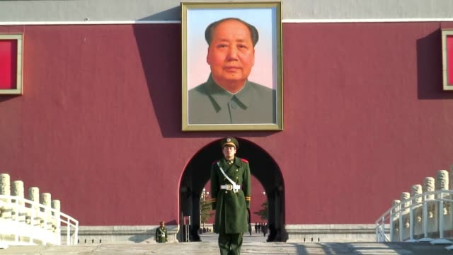 a guard stands beneath an image of chairman mao at the tiananmen gate in beijing. - tiananmen square stock videos and b-roll footage