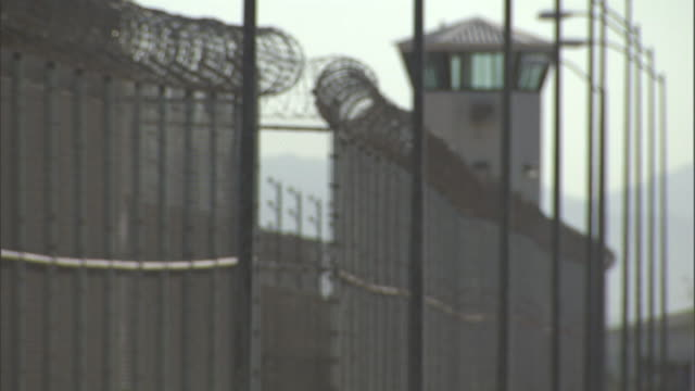a guard tower stands behind a fence topped by razor wire at a prison. - prison building stock videos & royalty-free footage