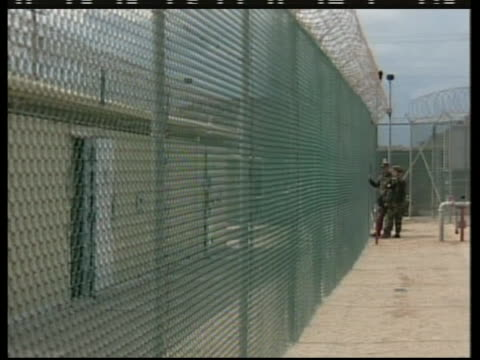 guards and detainees converse through a fence at the camp delta section of guantanamo bay - crime or recreational drug or prison or legal trial stock-videos und b-roll-filmmaterial