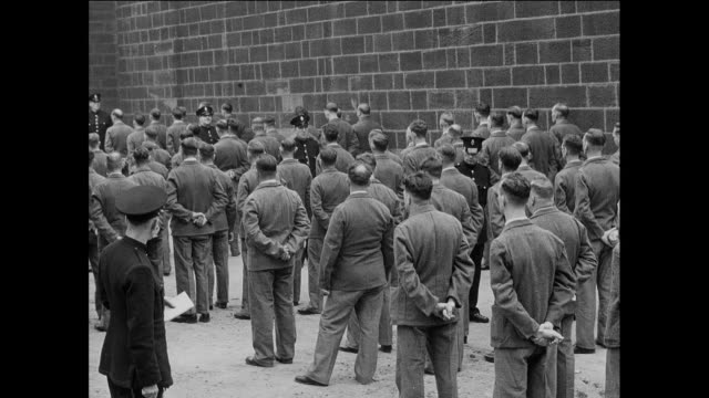 ws guards count and march prisoners in prison yard / uk / guard watches prisoners / prisoners at attention perform left turn / prisoners quick march and turn corner - prison education stock videos & royalty-free footage