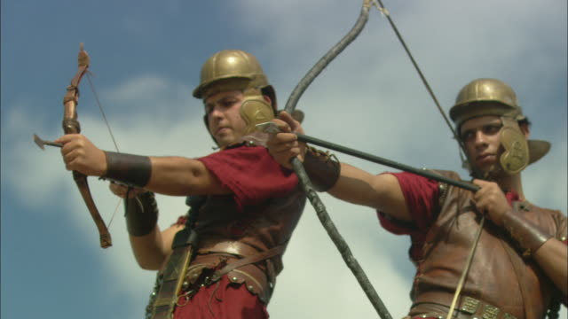 guards in period clothing aim their bows and arrows in unison. - bow and arrow stock videos and b-roll footage