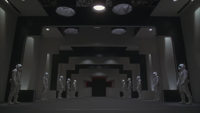 Guards in white bodysuits and masks stand motionless in a futuristic hallway, then suddenly swing their swords and run toward the camera.