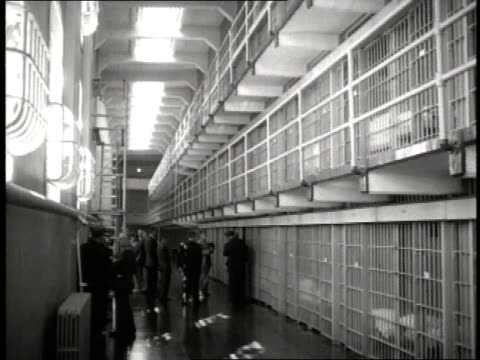 guards stand in front of prison cells on alcatraz as one guard pulls the level to open the door on a cell - alcatraz island stock videos & royalty-free footage